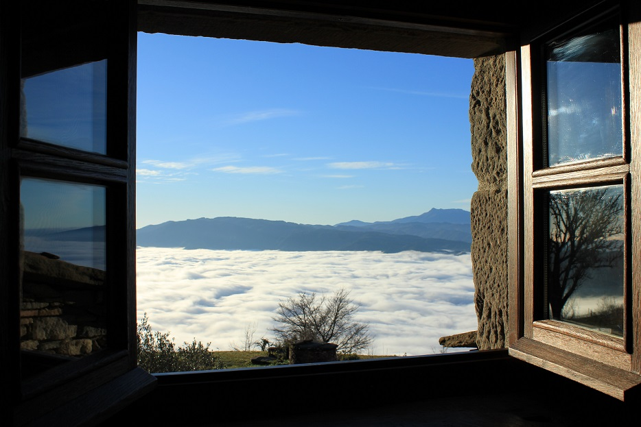 View from hill top window over low clouds